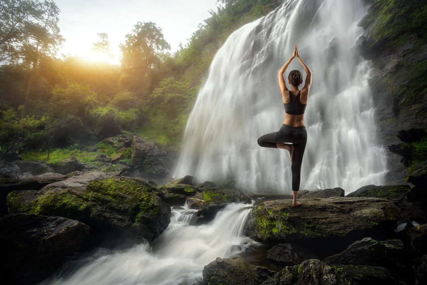 woman standing at waterfall healthy